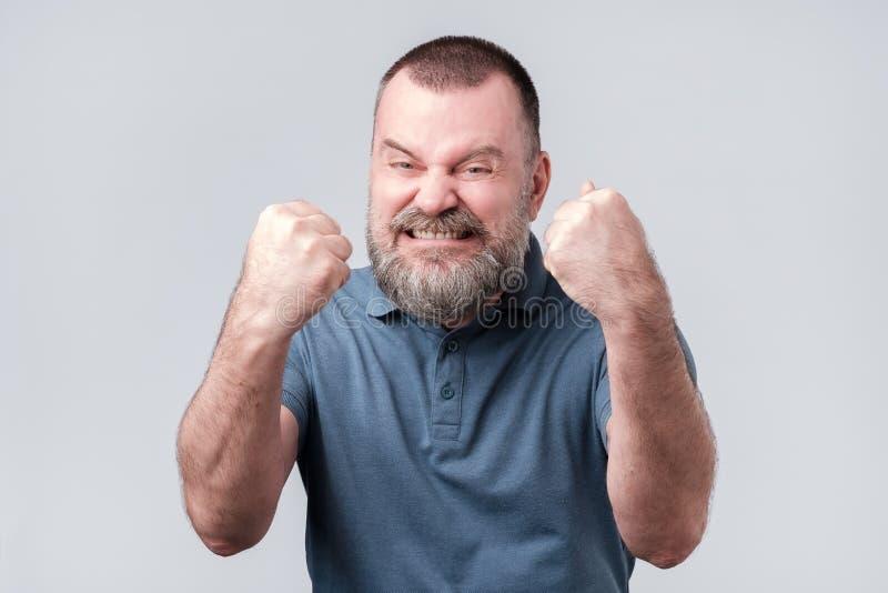 Lycklig mogen europeisk man som lyfter nävar upp att fira hans framgång arkivfoton