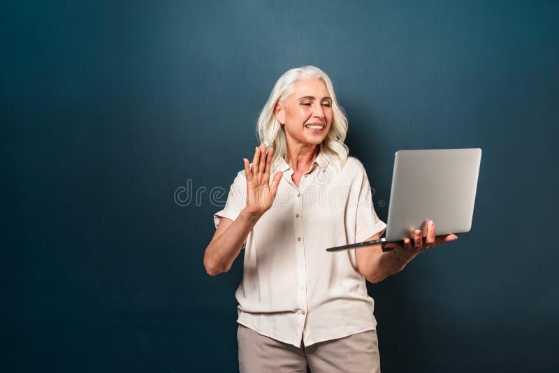 Lycklig mogen gammal kvinna som använder att vinka för bärbar datordator royaltyfria foton