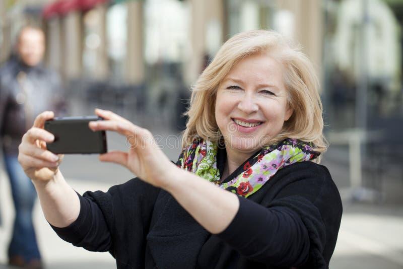 Lycklig mogen härlig blond kvinna som fotograferas på en mobiltelefon royaltyfria foton