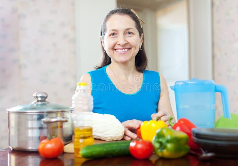 Lycklig mogen hemmafru med grönsaker fotografering för bildbyråer