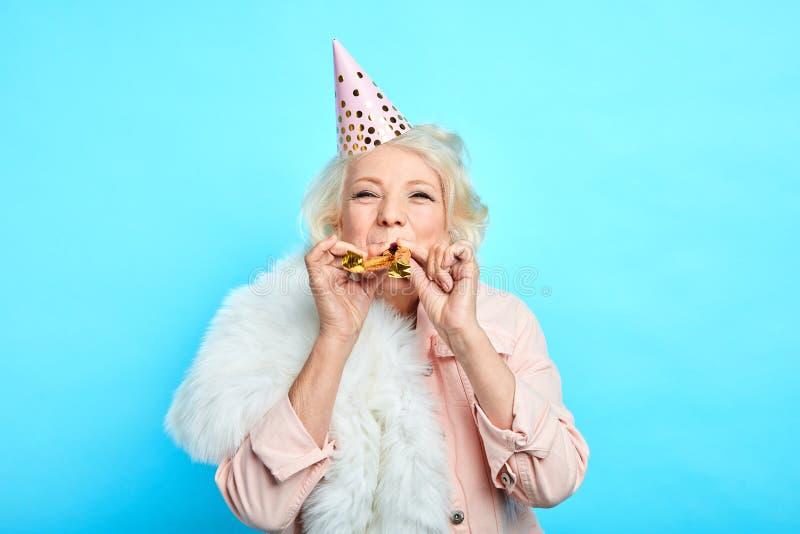 Lycklig mogen kvinna i partihatten som gör ett oväsen i partiet fotografering för bildbyråer
