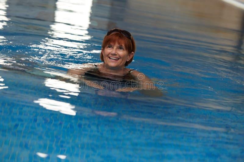 Lycklig mogen kvinna i simbassäng royaltyfri foto