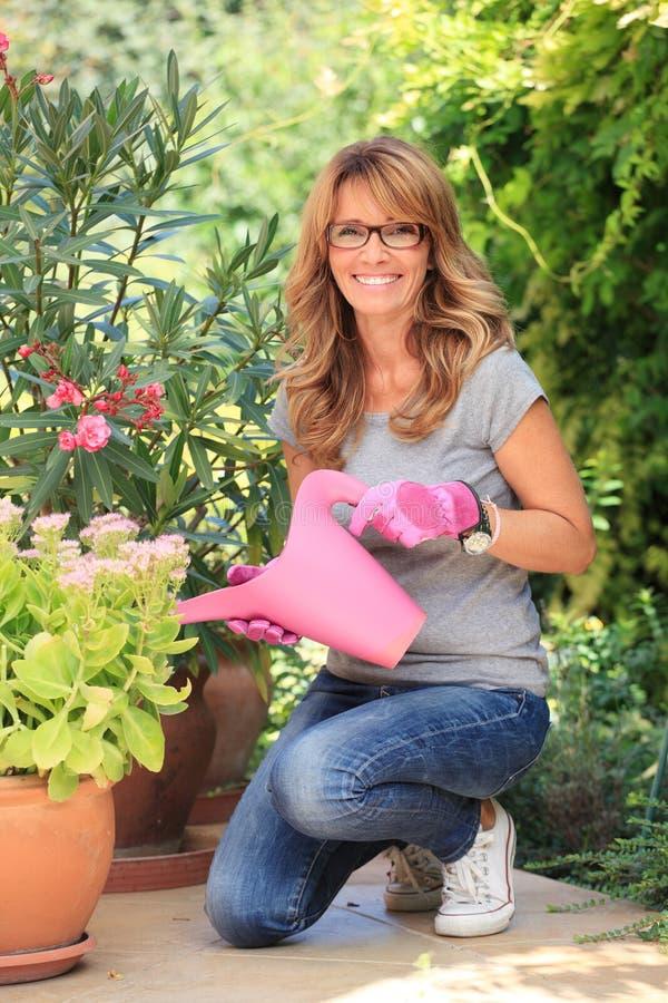 Lycklig mogen kvinna i trädgård royaltyfria bilder