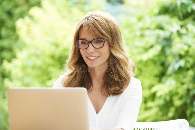 Lycklig mogen kvinna med bärbara datorn royaltyfri bild