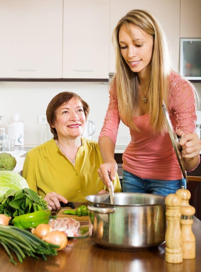 Lycklig mogen kvinna med den vuxna dottern som tillsammans lagar mat royaltyfri foto