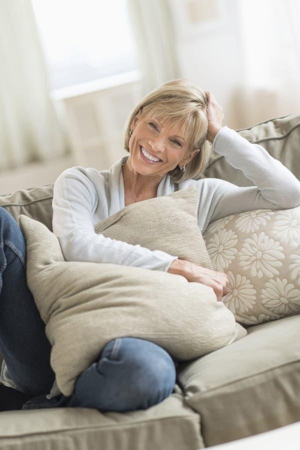 Lycklig mogen kvinna med kuddar som kopplar av på soffan royaltyfri foto