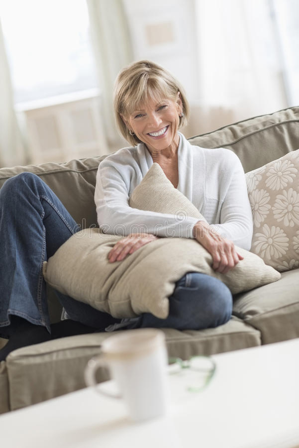Lycklig mogen kvinna med kuddesammanträde på soffan royaltyfria bilder