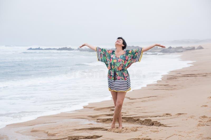 Lycklig mogen kvinna med utbredda armar som tycker om semester royaltyfri bild