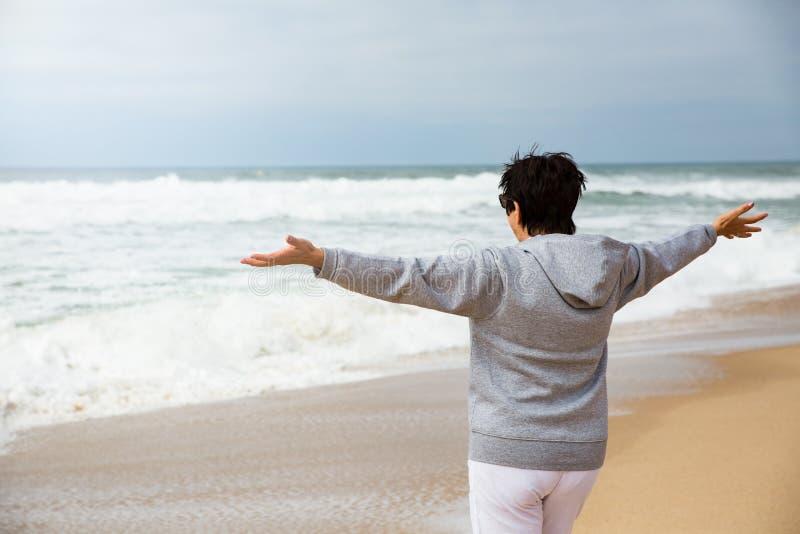 Lycklig mogen kvinna med utbredda armar som tycker om semester arkivbilder
