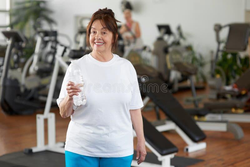Lycklig mogen kvinna med vatten på idrottshallen fotografering för bildbyråer
