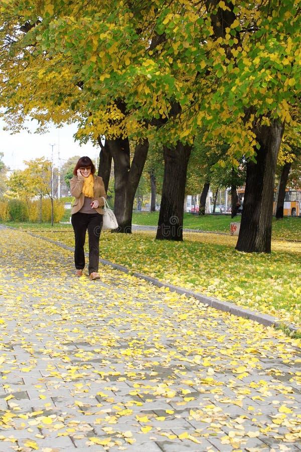 Lycklig mogen kvinna som går i parkera royaltyfri fotografi