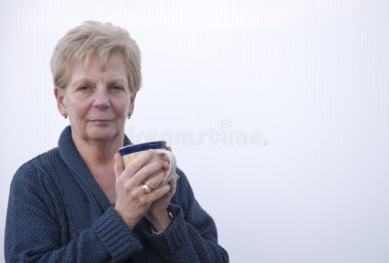 Lycklig mogen kvinna som rymmer en kopp kaffe royaltyfri bild