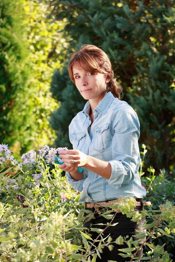 Lycklig mogen kvinna som tar omsorg av henne blommor royaltyfria bilder