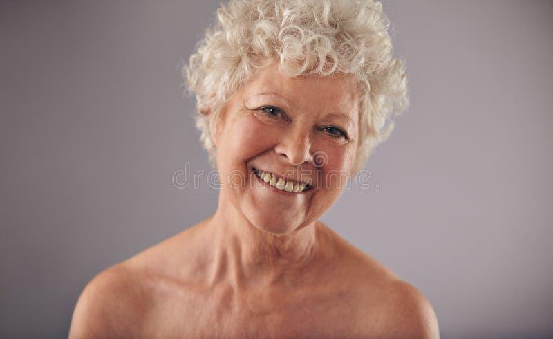 Lycklig mogen kvinnlig som ler på kameran fotografering för bildbyråer