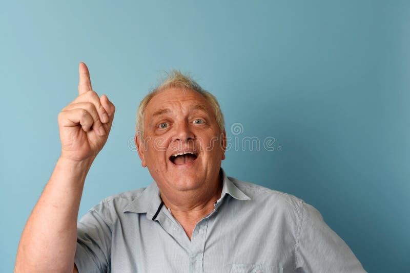 Lycklig mogen man som ler och pekar arkivbild
