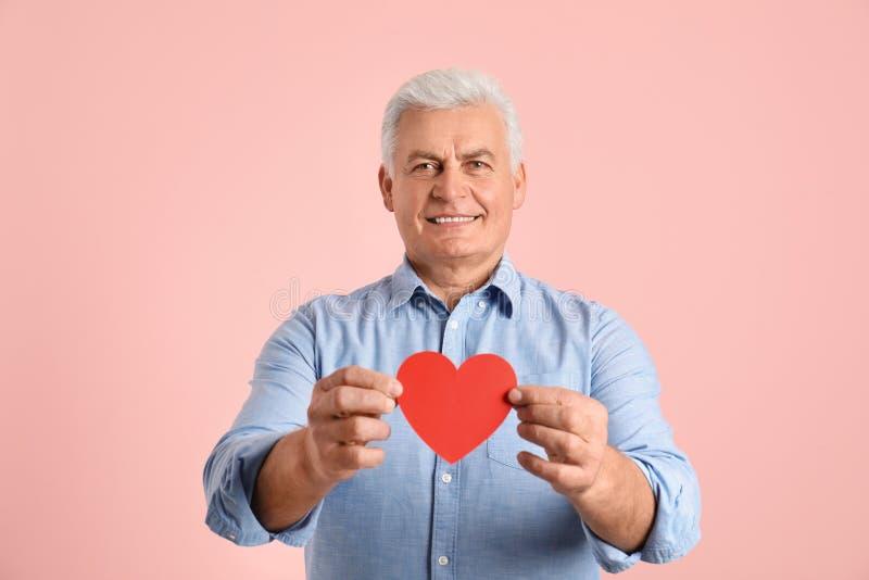 Lycklig mogen man som rymmer röd pappers- hjärta royaltyfri foto