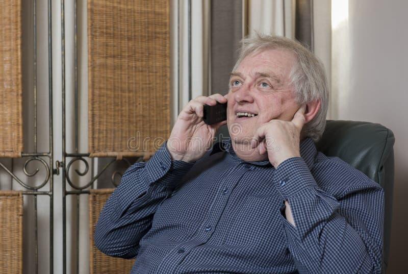 Lycklig mogen man som skrattar och talar på telefonen royaltyfri fotografi