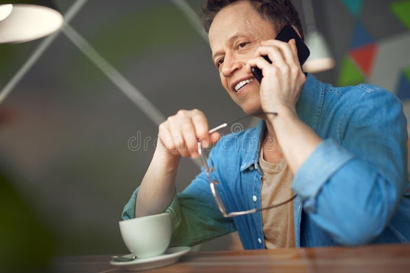 Lycklig mogen man som talar vid mobiltelefonen i kafé royaltyfri bild
