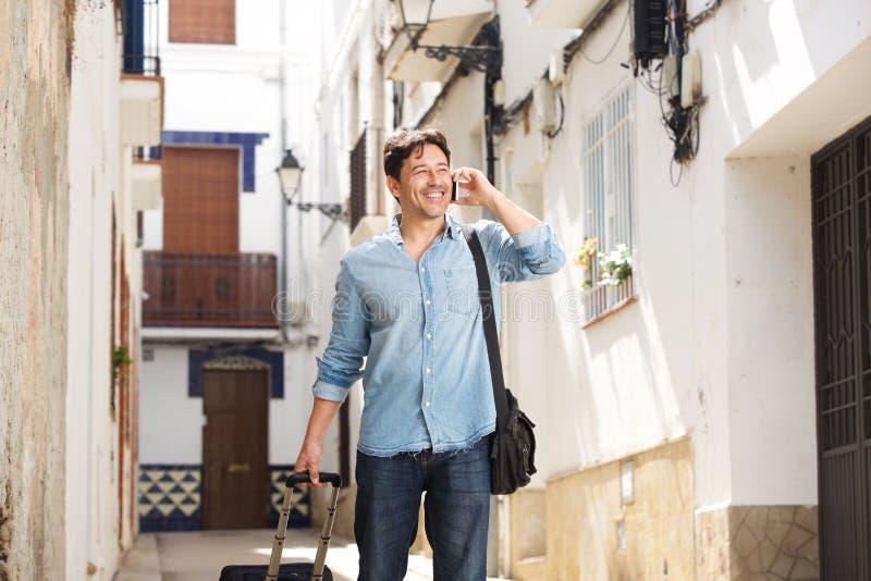 Lycklig mogen manlig handelsresande som går på gatan genom att använda mobiltelefonen arkivfoton