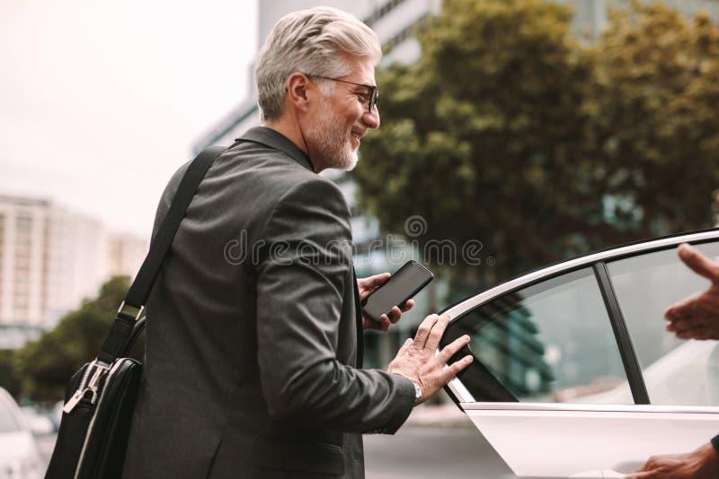 Lycklig mogen pendlare som får in i en taxi royaltyfri bild