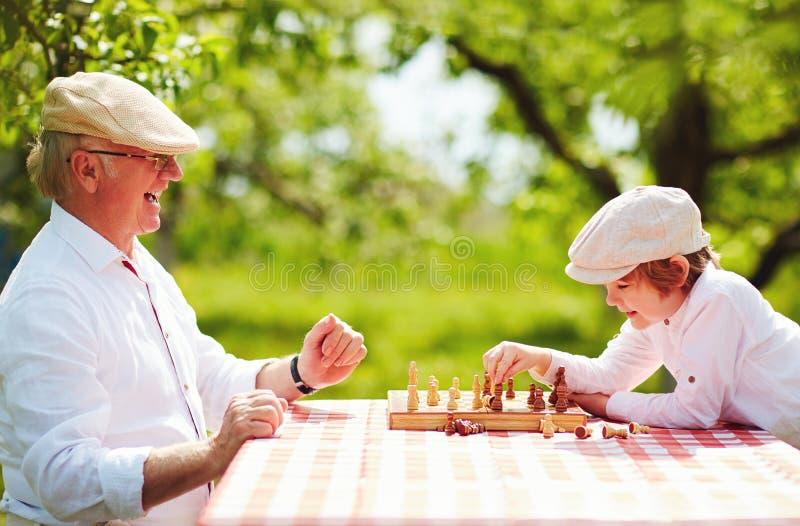 Lycklig morfar och sonson som spelar schack i vårträdgård royaltyfria bilder