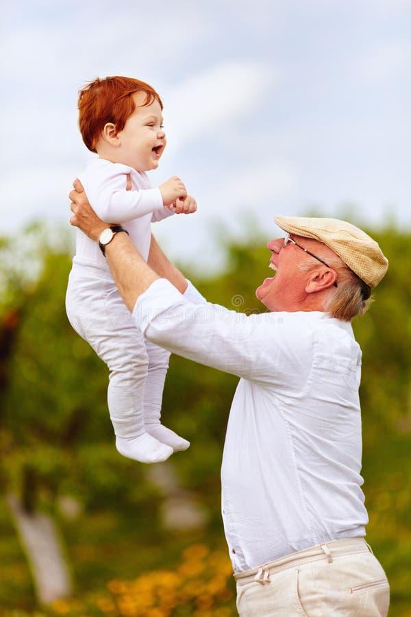 Lycklig morfar som spelar med den begynnande sonsonen i vårträdgård arkivfoton