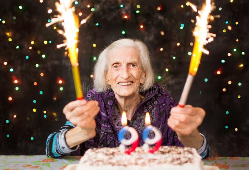 Lycklig mormor som firar den 99th födelsedagen med fyrverkerit arkivfoto