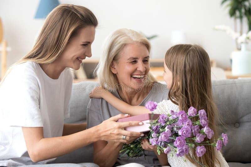 Lycklig mormor som tackar barnbarnet och den fullvuxna dottern för blommor arkivbild