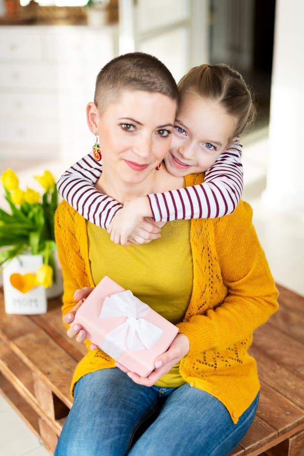 Lycklig mors dag- eller födelsedagbakgrund Förtjusande ung flicka som förvånar hennes mamma, unga cancerpatient, med buketten och arkivfoto