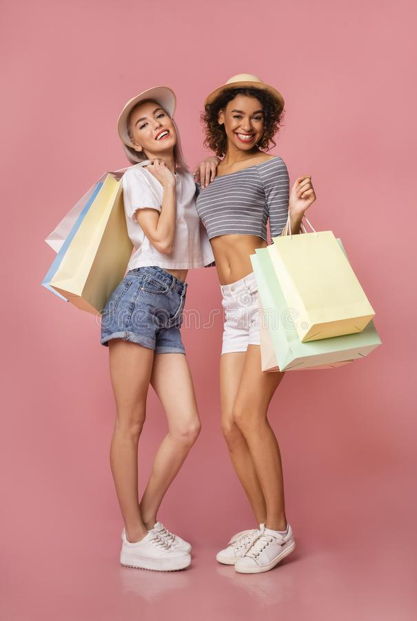 Lycklig multietnisk flickashopaholics med färgrika shoppa påsar arkivfoto