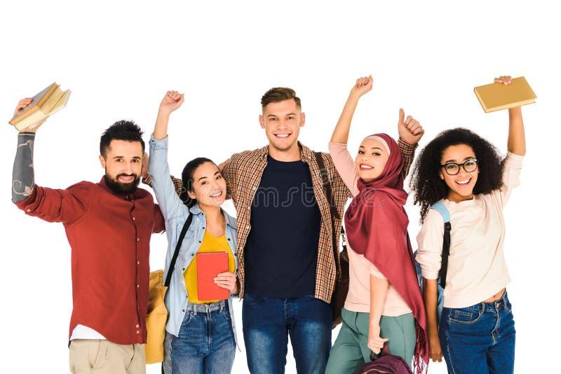lycklig multietnisk grupp av ungdomarsom rymmer böcker ovanför huvudet isolerade royaltyfria bilder