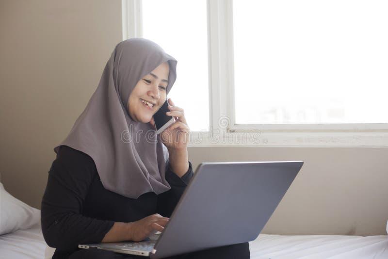 Lycklig muslimsk kvinna som arbetar med bärbara datorn och den smarta telefonen i hennes sovrum royaltyfria foton