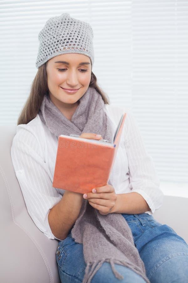Lycklig nätt brunett med vinterhatten på handstil på anteckningsboken royaltyfria bilder