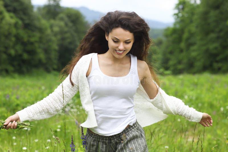 Lycklig nätt brunettkvinna i kamomillfältet, gulligt kvinnligt verkligt arkivbild