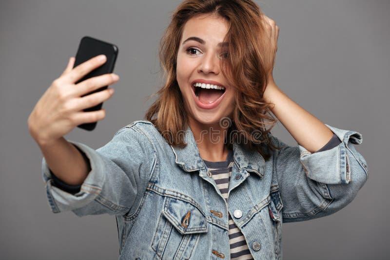 Lycklig nätt brunettkvinna som trycker på hennes hår, medan ta selfi fotografering för bildbyråer