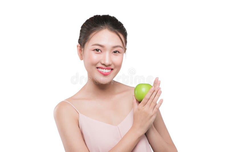 Lycklig nätt för showäpple för ung kvinna fördel till hälsa, asiatisk bea royaltyfria bilder