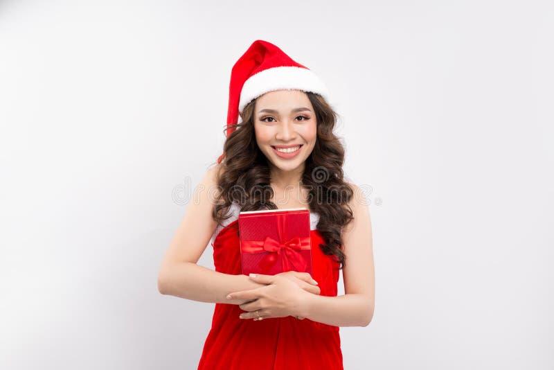 Lycklig nätt kvinna i röd klänning och hållande gåva för Santa Claus hatt royaltyfri bild