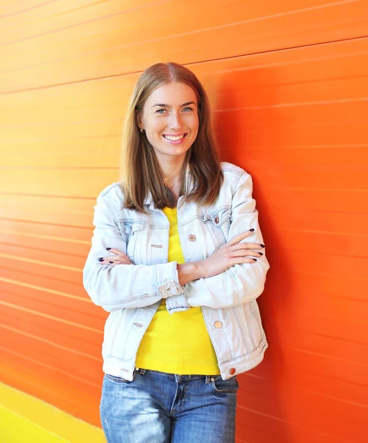 Lycklig nätt le kvinna för stående över den färgrika apelsinen arkivfoton