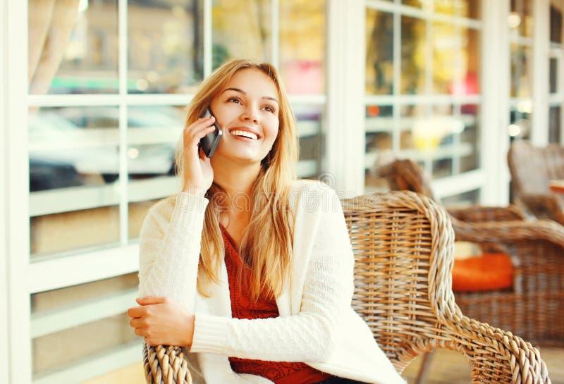 Lycklig nätt le kvinna som talar på smartphonen i kafét arkivbild