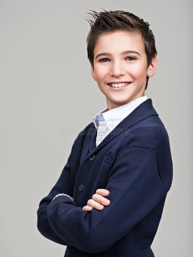 Lycklig nätt tonårs- pojke som poserar på studion royaltyfri bild