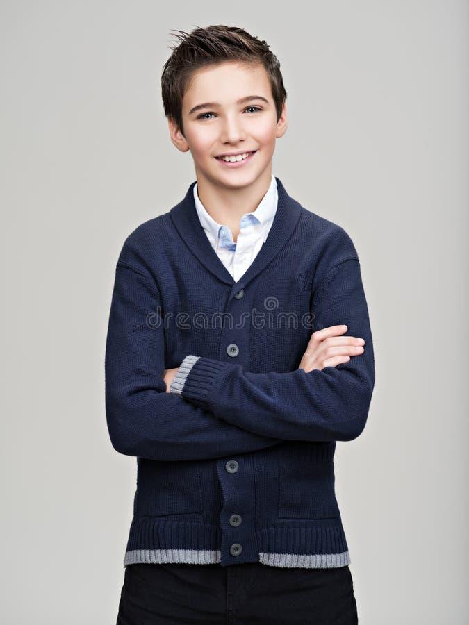 Lycklig nätt tonårs- pojke som poserar på studion arkivfoton