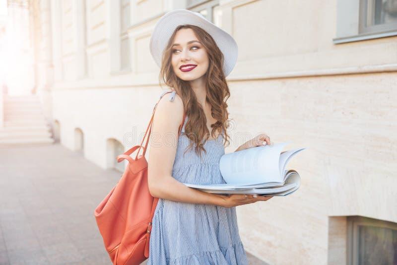 Lycklig nätt ung kvinna som läser en bok på gatan arkivbild