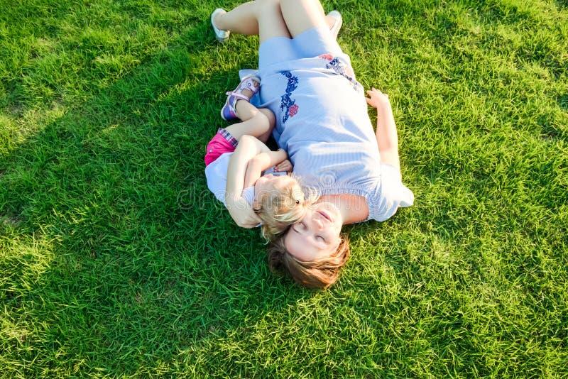 lycklig natur för familj Mamman och lilla barnet behandla som ett barn dottern som lägger och kopplar av som kramar, på äng för g arkivfoton