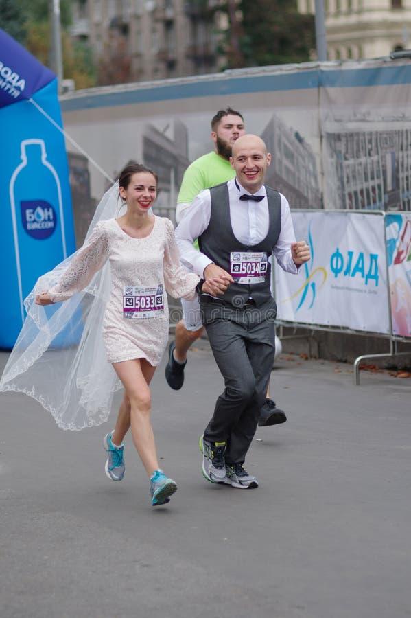 Lycklig nyligen gift parspring på en stadsgata under 5 km avstånd av maraton för ATB Dnipro royaltyfri foto