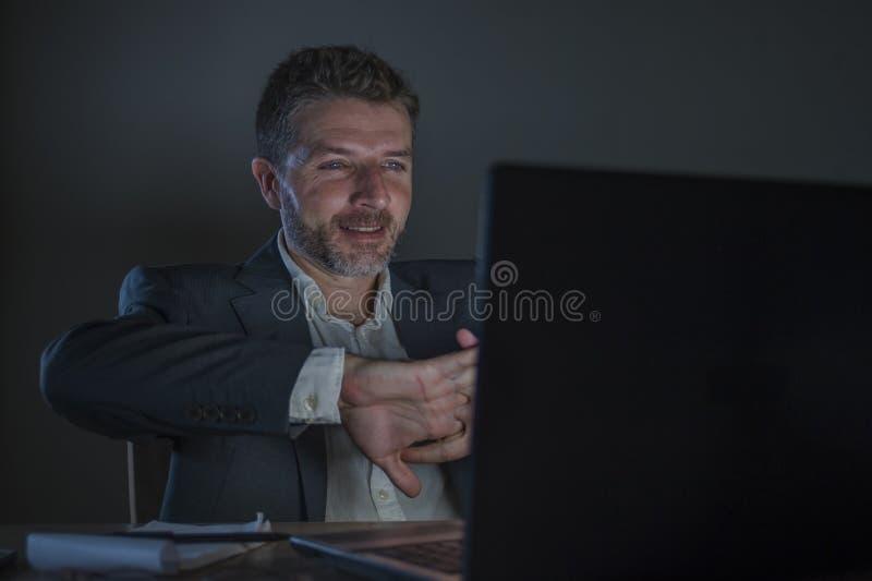Lycklig och attraktiv affärsman som sent firar framgång i gladlynt och upphetsad natt för framsidauttrycksarbete - på kontorsbärb arkivfoto