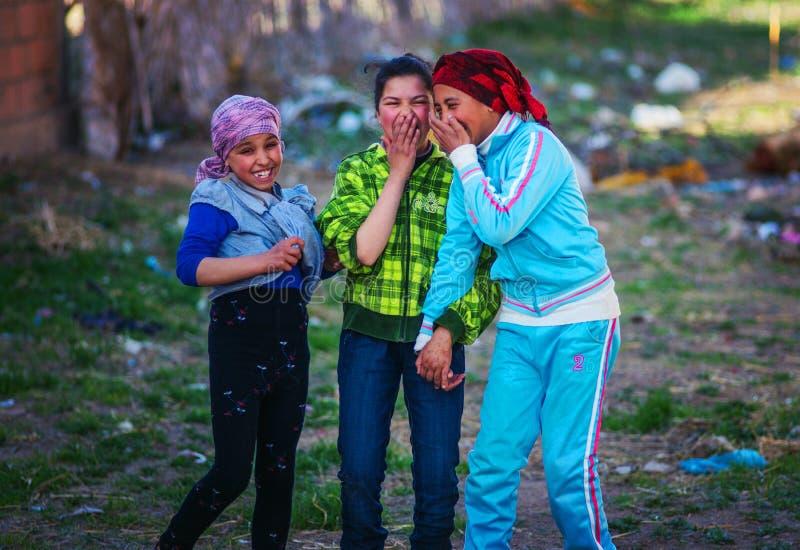 Lycklig och färgrik islamflicka med den gamla traditionella muslinklänningen i den Marocko byn royaltyfria foton