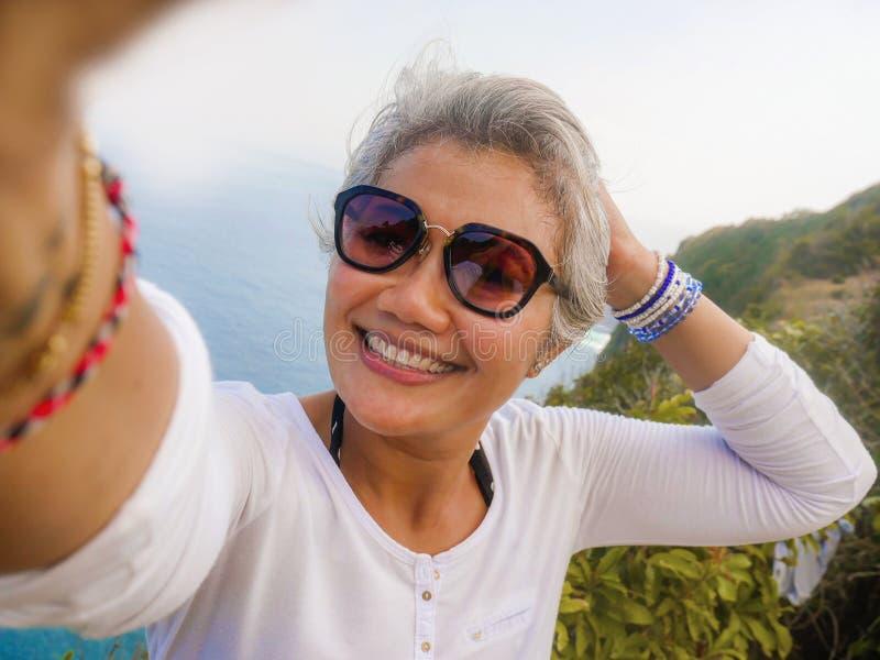 Lycklig och gladlynt asiatisk kvinna för mellersta ålder50-tal med grått hår som tar selfie med mobiltelefonen på den härliga tro arkivbilder