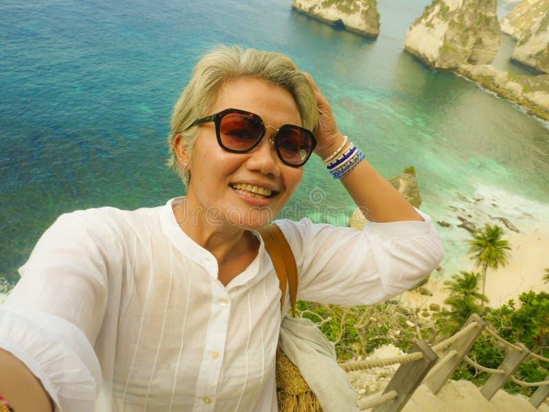 Lycklig och gladlynt asiatisk kvinna för mellersta ålder50-tal med grått hår som tar selfie med mobiltelefonen på den härliga tro arkivfoto