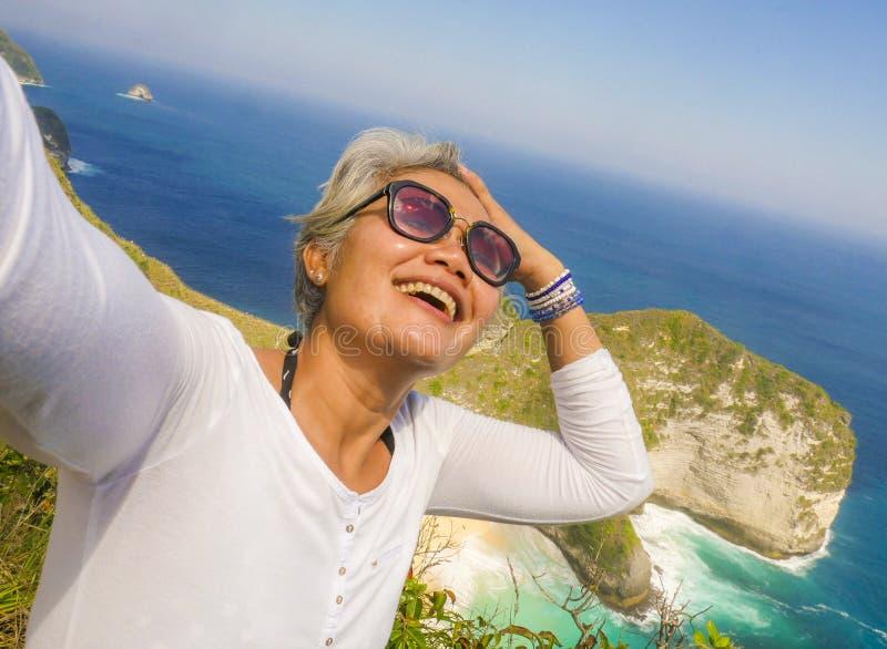 Lycklig och gladlynt asiatisk kvinna för mellersta ålder50-tal med grått hår som tar selfie med mobiltelefonen på den härliga tro arkivfoton