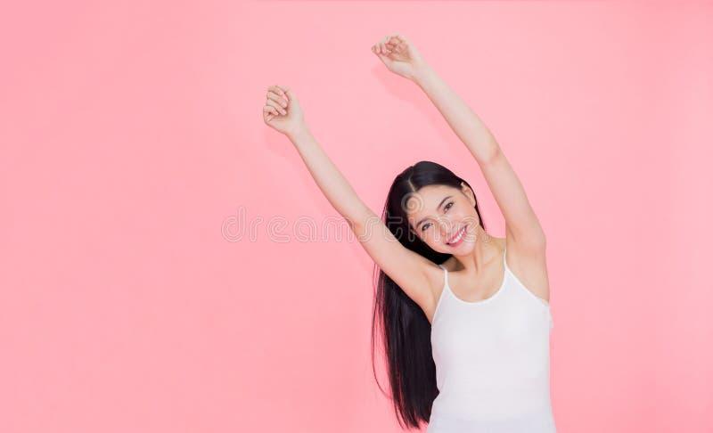 Lycklig och gladlynt le asiatisk 20-talkvinna som lyfter upp händer för positiv känsla och beröm som isoleras över rosa bakgrund royaltyfri fotografi